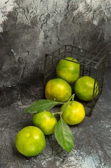 Vista verticale del cesto caduto con mandarini verdi freschi su sfondo grigio immagine stock