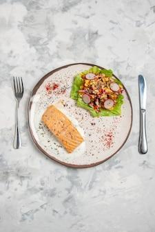 Vista verticale di farina di pesce e deliziosa insalata su un piatto e posate su una superficie bianca macchiata