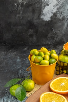 Vertical view of fresh citrus fruits with knife on wooden cutting board on newspaper on gray background