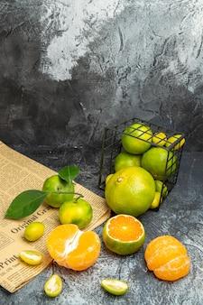Vista verticale di agrumi freschi con foglie cadute da un cesto nero tagliato a metà su un giornale su sfondo grigio