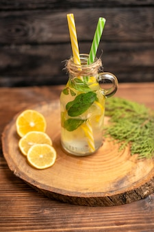 Vertical view of fresh detox water in a glass served with tubes and lemon limes on a brown tray