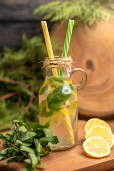Vertical view of fresh detox water in a glass served with tubes and lemon limes on a wooden cutting board on a brown table