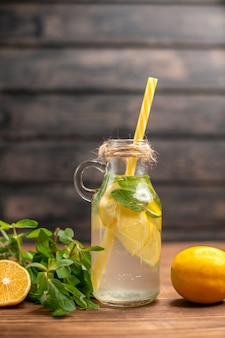 Vertical view of fresh detox water served with tube mint and orange on a brown background