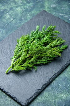 Vertical view of fresh dill bundle on black cutting board on green black mix colors background