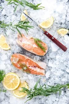 Vista verticale del pesce fresco diviso in due parti con fette di limone su ghiaccio