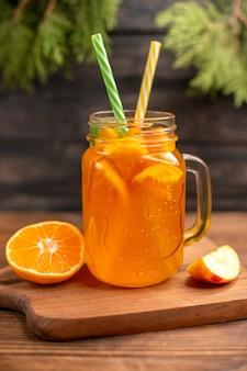 Vista verticale del succo di frutta fresca in un bicchiere servito con tubi e mela e arancia su un tagliere di legno su un tavolo marrone