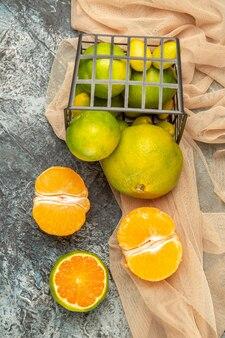 Vista verticale di limoni freschi in un cesto nero caduto su un asciugamano su un tavolo grigio fotografia stock