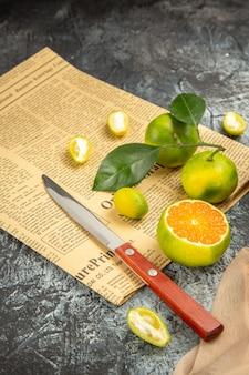 Vista verticale di limoni freschi in un cesto nero caduto su coltello asciugamano e giornale su tavolo grigio