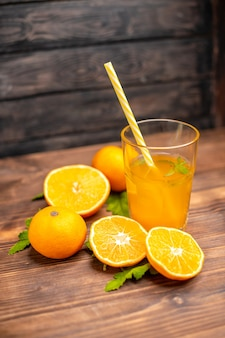 Vertical view of fresh orange juice in a glass served with tube mint and whole cut oranges on the left side on a wooden table