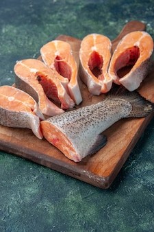 Vertical view of fresh raw fishes on brown wooden cutting board on dark mix colors table with free space