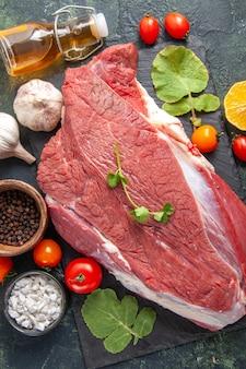 Vista verticale di carne rossa cruda fresca sul coltello da bottiglia di olio caduto verdure di pepe del vassoio nero su sfondo di colore scuro
