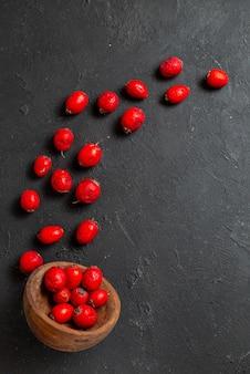 Vista verticale delle bacche rosse fresche del corniolo che versano fuori la ciotola marrone sul nero