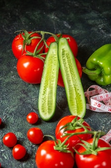 Vertical view of fresh tomatoes peppers and meter cucumbers on dark colors surface with free space