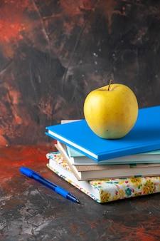 어두운 배경의 왼쪽에 쌓인 노트북의 세로 보기 신선한 노란색 사과