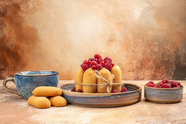 Vista verticale della torta morbida appena sfornata con frutta e tè in una tazza blu sulla tabella dei colori misti