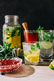 Vertical view of freshly-made cold drinks with fruits and mint on the table