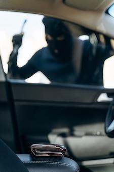 검은 옷을 입은 남자가 머리에 발라클라바를 하고 도둑질하기 전에 지렛대로 차 한 잔을 깨려고 준비하는 차에서 수직으로 바라본 모습. 자동차 도둑, 자동차 절도 개념