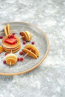Vista verticale della decorazione frittella di frutta per la colazione sul piatto bianco