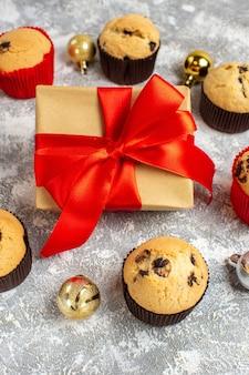 Vista verticale del regalo con nastro rosso tra deliziosi piccoli cupcakes appena sfornati e accessori decorativi sul tavolo del ghiaccio