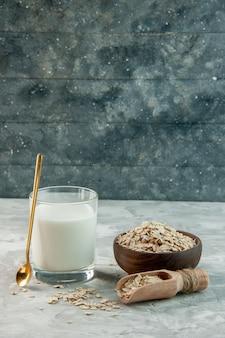 Vista verticale della tazza di vetro piena di latte e avena dentro e fuori la pentola marrone su sfondo grigio