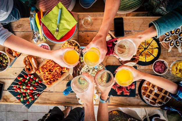 Vertical above view of group of friends differente ages clinking and toasting with glasses - table full of food in the background - party at home to celebrate together in friendship - having fun toget