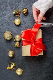 Vista verticale della mano che taglia un nastro rosso sulla confezione regalo e accessori decorativi su sfondo scuro