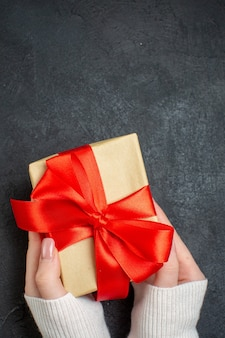 Vertical view of hand holding beautiful gift with bow-shaped ribbon on dark background