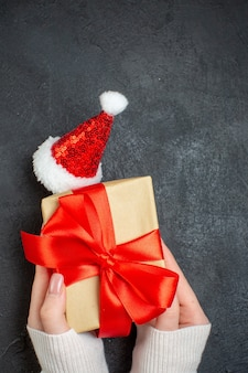 Vertical view of hand holding beautiful gift with bow-shaped ribbon next to santa claus hat on dark background