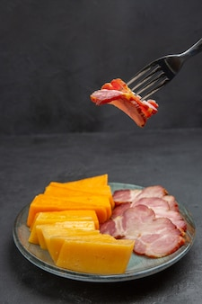 Вертикальный вид руки, принимающей еду вилкой из синей тарелки с вкусными закусками на черном фоне