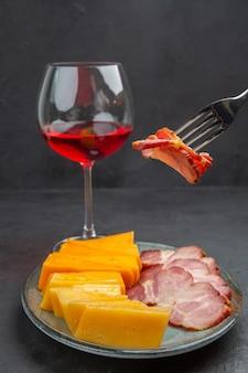 Vista verticale mano prendendo un alimento con la forchetta da un piatto blu con deliziosi snack e vino rosso in calice di vetro su sfondo nero