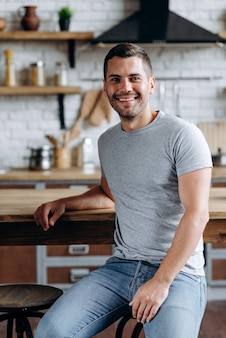 Vertical view of the handsome man sitting on the chair leaned on table, smiling and looking at the camera. image at the cozy kitchen
