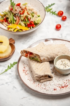 Vista verticale di insalate vegane sane ananas essiccato e impacchi lavash sulla superficie bianca macchiata