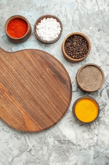 Vertical view of healthy wooden cutting board different spices on white background