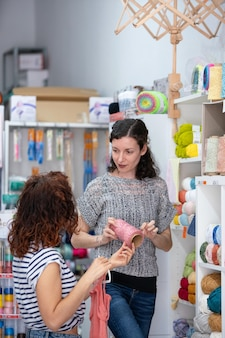 Vertical view of help assistant on a retail shop helping a woman to buy a ball of pink yarn