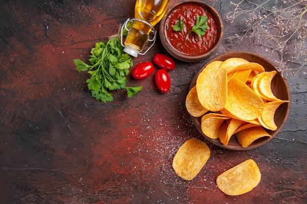 Vista verticale di patatine fritte deliziose fatte in casa in una piccola ciotola marrone olio caduto verde bottiglia e pomodori ketchup all'aglio sul tavolo scuro