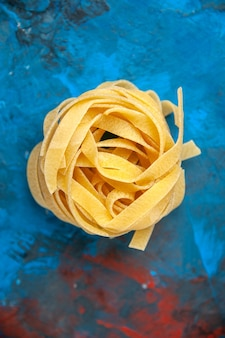 Vertical view of homemade fresh tagliatelle pasta on blue background