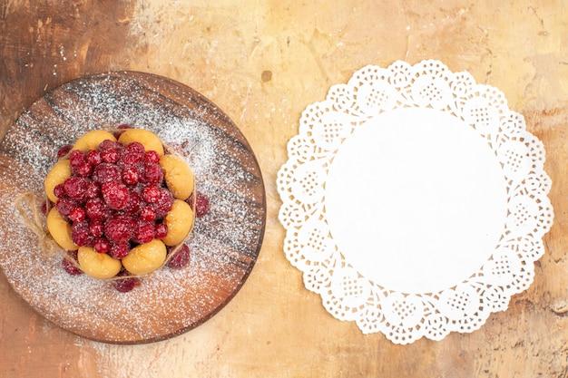 Vista verticale della torta morbida fatta in casa con frutta e tovagliolo sul tagliere di legno sulla tavola di colori misti