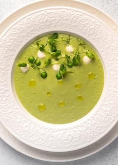 녹색 완두콩의 세로보기 수제 스프 퓨레, 흰색의 미니 모짜렐라 치즈와 코코넛 밀크
