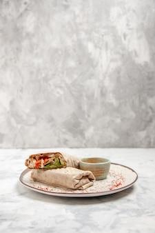 Vista verticale dell'involucro di lavash e yogurt in una piccola ciotola su un piatto sulla superficie bianca macchiata