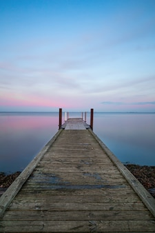 Vertical view of a long wooden pier near the ocean under the pastel-colored sky