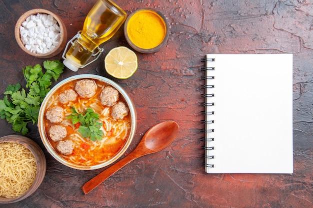 Vista verticale della zuppa di polpette con tagliatelle in una ciotola marrone cucchiaio di limone un mucchio di pasta verde e bottiglia di olio e taccuino sul tavolo scuro
