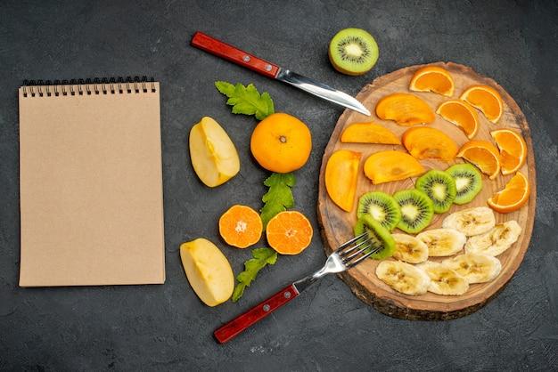 Vista verticale della frutta fresca organica naturale allegata sul tagliere intorno ad essa accanto al quaderno a spirale su superficie scura