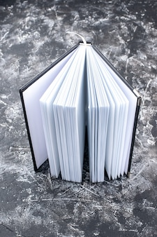 Vertical view of new open book with clean empty pages lies on distressed dark wall background