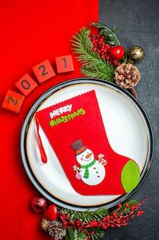 Vista verticale dello sfondo del nuovo anno con il calzino di natale sulla decorazione del piatto della cena accessori rami di abete e numeri su un tovagliolo rosso su una tavola nera