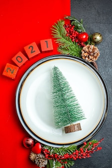 Vertical view of new year background with christmas tree dinner plate decoration accessories fir branches and numbers on a red napkin on a black table