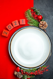 Vista verticale del fondo del nuovo anno con i rami e i numeri dell'abete degli accessori della decorazione del piatto di cena su un tovagliolo rosso su una tavola nera