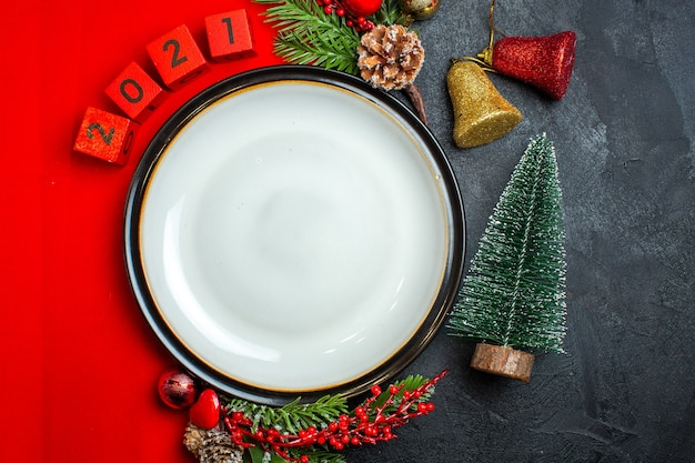 Vertical view of new year background with dinner plate decoration accessories fir branches and numbers on a red napkin next to christmas tree on a black table