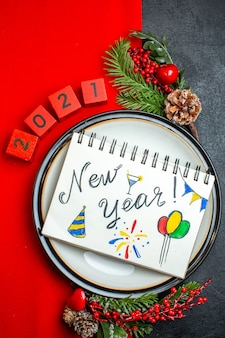 Vertical view of new year background with notebook with new year drawings on a dinner plate decoration accessories fir branches and numbers on a red napkin on a black table