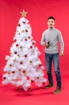 Vertical view of new year mood with positive guy singing song standing near decorated christmas tree on red