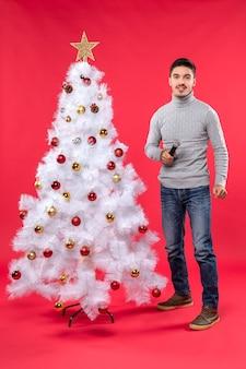 Vista verticale dell'umore del nuovo anno con il ragazzo positivo che canta la canzone che sta vicino all'albero di natale decorato sul rosso
